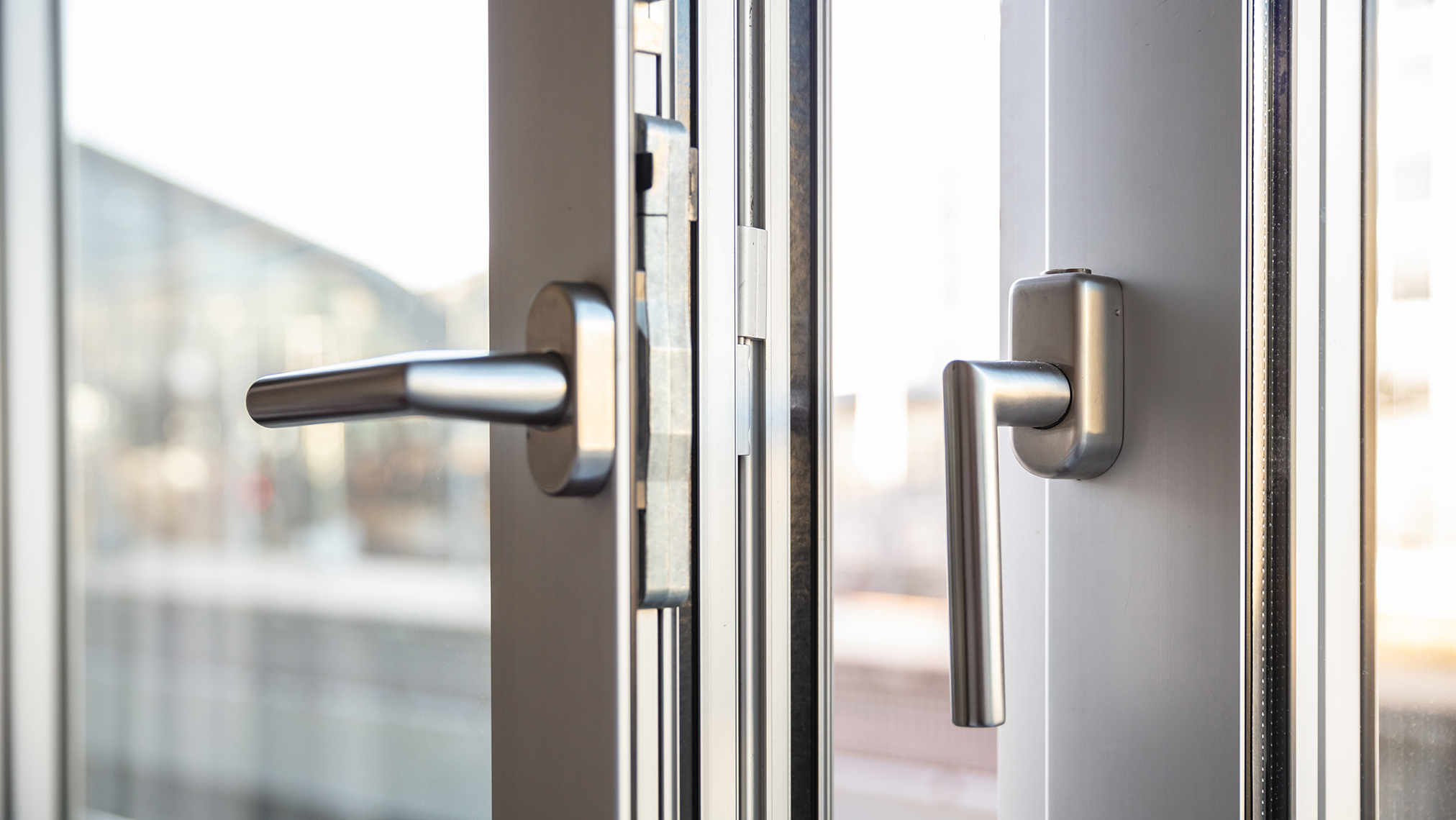 Close up view of aluminum door window handles, against a blurry background